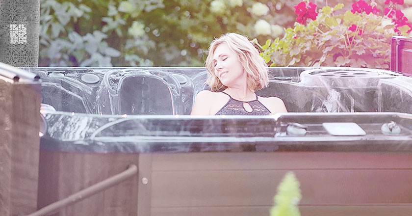 Woman enjoying her hot tub in her back yard
